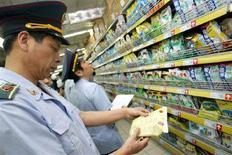 <p>Degli ispettori cinesi controllano confezioni di latte in polvere in un supermercato. REUTERS/China Photos</p>