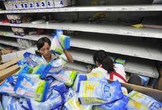 <p>Commesse rimuovono dagli scaffali di un supermercato i prodotto contaminati con la melammina, a Hefei, provincia di Anhui, il 16 settembre del 2008. REUTERS/Stringer</p>