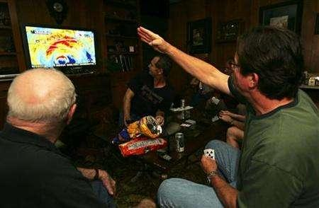 Residents of southwest Louisiana, including Buzz Bonnet (R), watch a television report on Hurricane Rita's progress as they play cards in Elton, Louisiana September 23, 2005. REUTERS/Lee Celano
