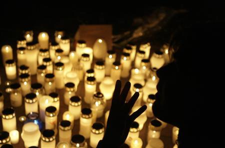 A man gestures at front of candles placed near a vocational school in Kauhajoki about 217 miles from Helsinki September 24, 2008. REUTERS/Ints Kalnins