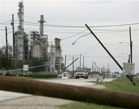 Power lines knocked down by Hurricane Ike are seen in front of an oil refinery in Pasadena, Texas, September 15, 2008. REUTERS/Jessica Rinaldi