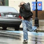 <p>A man fights through high winds and rain created by Hurricane Kyle in the town of Yarmouth, Nova Scotia, September 28, 2008. REUTERS/Paul Darrow</p>