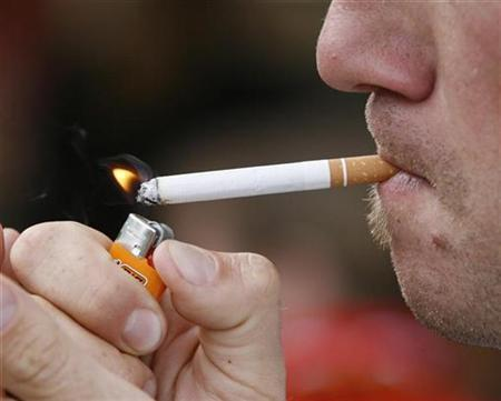A smoker lights up a cigarette in a public place near the Stade de Geneve in Geneva August 22, 2007. REUTERS/Denis Balibouse