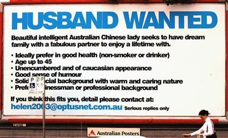 A woman walks past a billboard that Shanghinese woman Helen Zhou placed in search of a husband in Sydney October 21, 2004. REUTERS/David Gray