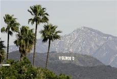 <p>The Hollywood Sign is seen between palm trees and snow dusted mountains in Los Angeles January 7, 2008. REUTERS/Danny Moloshok</p>