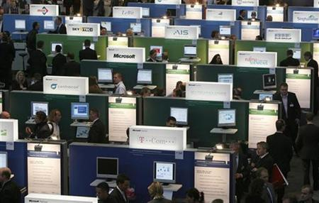 Visitors stand between rows of computers at the Microsoft booth during the first public day at the CeBIT computer fair in Hanover March 15, 2007. REUTERS/Christian Charisius