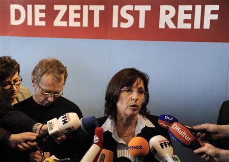 Hesse's Social Democratic Party (SPD) leader Andrea Ypsilanti answers reporter's questions while standing under a logo ''The time is right'' after an extraordinary party convention in Rotenburg an der Fulda, October 4, 2008. Social Democrats in the German state of Hesse on Saturday backed a plan to form a coalition with the Greens with support from a far-left party, paving the way for them to oust Chancellor Angela Merkel's conservatives in the state. REUTERS/Kai Pfaffenbach(GERMANY)