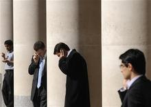 <p>Impiagati parlano al telefono, in un'immagine d'archivio. REUTERS/Toby Melville</p>