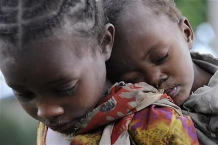 A girl carries her brother as she waits for food distribution in Buge village, Wolayita region in southern Ethiopia in this picture taken on September 8, 2008 and released by the International Federation of Red Cross and Red Crescent Societies (IFRC) on September 23, 2008. REUTERS/Jose Cendon/IFRC