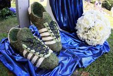 <p>Soccer boots made of grass are displayed during the opening ceremony of a specially designated cemetery section for HSV fans at the Altona cemetery near the stadium in Hamburg in this September 9, 2008 file photo. Hamburg SV is the first soccer club in Europe to have a cemetery for its fans. They can be buried close to their team's home stadium in a coffin for about 2,350 euros or they can have their ashes buried in a club urn for about 390 euros. Picture taken September 9, 2008. To match feature SOCCER/GRAVEYARD REUTERS/Christian Charisius/Files</p>