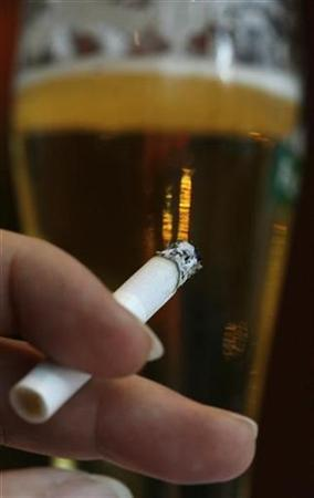 A woman smokes a cigarette in a bar in downtown Zurich in this file photo fromSeptember 28, 2008. REUTERS/Christian Hartmann