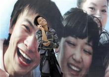 <p>Un uomo al cellulare davanti a un cartellone pubblicitario a Pechino. REUTERS/Jason Lee</p>
