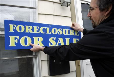 Marc Charney, president of CharneyRealEstate.com, hangs a sign reading ''Foreclosure For Sale'' on a house in the Boston suburb of Dedham, Massachusetts, in this March 15, 2007 file photo. REUTERS/Brian Snyder/Files