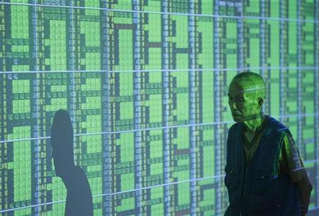 A man walks past stock market monitors in Taipei October 13, 2008. REUTERS/Nicky Loh