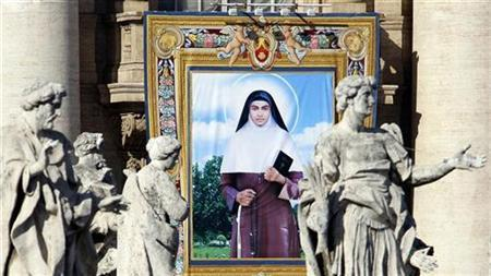 A tapestry depicting Sister Alphonsa of the Immaculate Conception is seen among the statues of St. Peter's Colonnade during the canonization ceremony led by Pope Benedict XVI in St. Peter square at the Vatican October 12, 2008. REUTERS/Alessandro Bianchi
