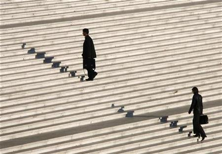 Businessmen climb stairs under the Arche de la Defense as they arrive for work in the financial district west of Paris October 9, 2008. REUTERS/John Schults