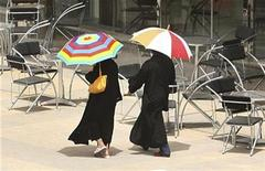 <p>Women walk past an empty coffee shop during summer, with temperatures rising above 42 degrees Celsius (108 degrees Fahrenheit) in Riyadh, July 12, 2007. REUTERS/Ali Jarekji</p>