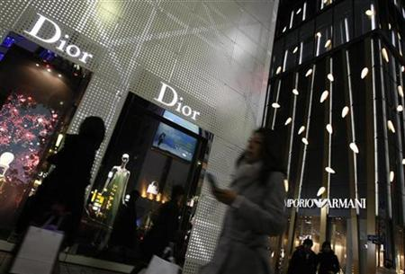 Passersby walk in front Christian Dior (L) and Armani Ginza Tower at Tokyo's Ginza shopping and amusement district in this December 30, 2007 file photo. REUTERS/Issei Kato/Files