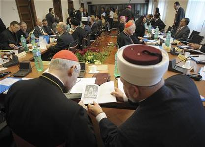 A Cardinal (L) looks at a religious book with a Muslim scholar during a meeting at the Vatican November 4, 2008. REUTERS/Osservatore Romano