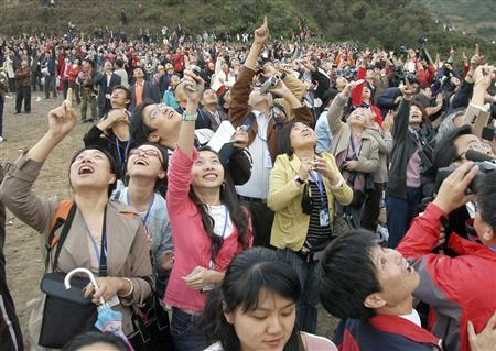 Spectators watch a Long March 3A rocket carrying the Chang'e One lunar orbiter blasting off, near the Xichang Satellite Launch Center, in southwestern Sichuan province. October 24, 2007. REUTERS/China Daily