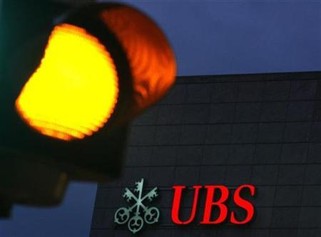 The logo of Swiss bank UBS is pictured behind a traffic light, on a building in Zug, October 17, 2008. REUTERS/Michael Buholzer