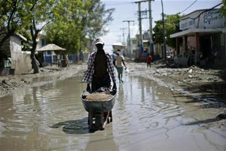 A Haitian pushes a wheelbarrow through a flooded street in the town of Gonaives September 21, 2008. REUTERS/ Eduardo Munoz