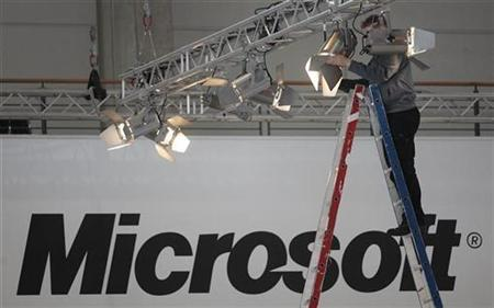 A worker fixes a spotlight at the Microsoft exhibit of the CeBIT fair in Hanover in this March 3, 2008 file photo. REUTERS/Hannibal Hanschke