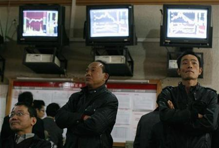 People stand in front of screens showing stock information at a brokerage house in Wuhan, Hubei province November 18, 2008. REUTERS/Stringer