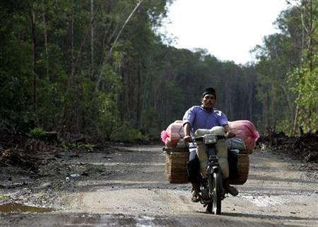 An Acehnese vendor rides a motorcycles through the new road at a forest near the Indonesia town of Calang June 19, 2005. REUTERS/Beawiharta