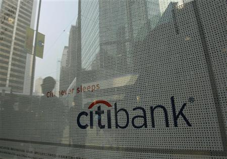 Pedestrians are reflected in the window of a Citibank branch in Hong Kong's financial Central District November 18, 2008. REUTERS/Bobby Yip