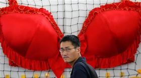 <p>Un uomo passeggia davanti a un enorme reggiseno in un'immagine di archivio. REUTERS/Leo Lang</p>