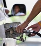 <p>Un benzinaio fa il pieno a un cliente REUTERS/Sukree Sukplang (THAILAND)</p>