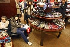 <p>An exhausted woman takes a break in the tie department as holiday shoppers crowd Macy's department store in New York November 23, 2007. REUTERS/Ray Stubblebine</p>