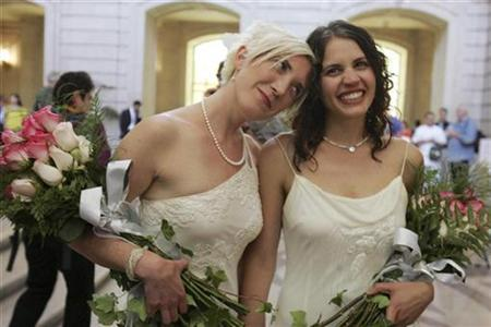 Newlyweds Sharon Papo (R) and Amber Weiss walk through City Hall after exchanging wedding vows in San Francisco, California June 17, 2008. REUTERS/Erin Siegal