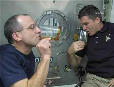 Space Shuttle Endeavour astronauts Don Pettit (L) and Stephen Bowen drink after making a Thanksgiving toast from aboard the International Space Station (ISS) in this November 27, 2008 image from NASA TV. REUTERS/NASA TV