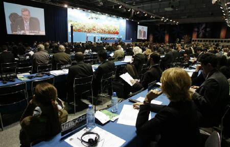 Delegates listen to a speech during a session of the U.N. climate change conference in Poznan December 1, 2008. The economic slowdown is ''no excuse'' to neglect a fight against global warming that could widen water shortages to half the world by 2050, delegates told the opening of U.N. climate talks in Poland on Monday. REUTERS/Kacper Pempel