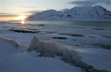 The sun shines low in the sky just after midnight over a frozen coastline near the Norwegian Arctic town of Longyearbyen, April 26, 2007. REUTERS/Francois Lenoir