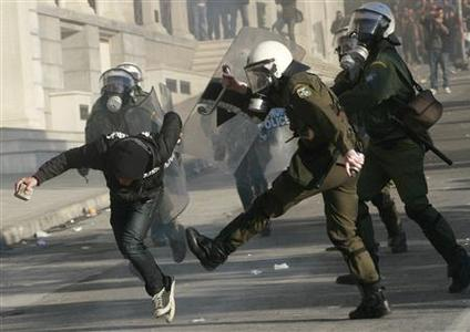 A protester tries to escape from riot policemen during a demonstration in Athens December 9, 2008. REUTERS/John Kolesidis