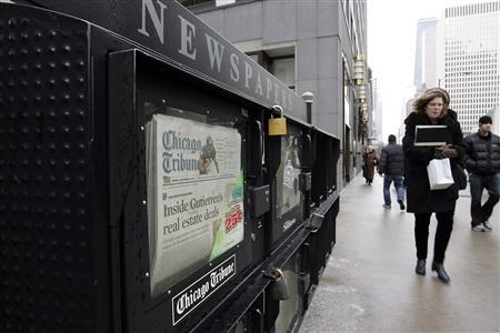 People walk past a newspaper box across from the Chicago Tribune tower in Chicago, Illinois December 8, 2008. REUTERS/Frank Polich
