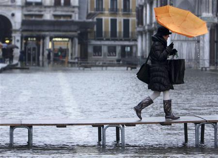 A pedestrian uses a raised walkway to pass over the flooded Saint Mark's square during a period of high water in Venice December 10, 2008. REUTERS/Manuel Silvestri