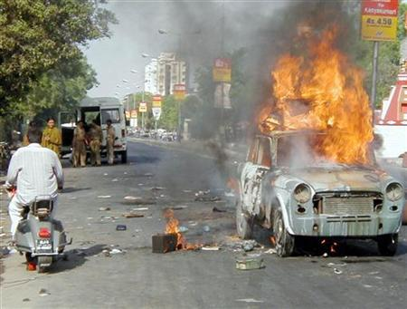 An Indian man rides past a burning car during a riot in the city of Ahmedabad in the western state of Gujarat, May 5, 2002. REUTERS/Amit Dave