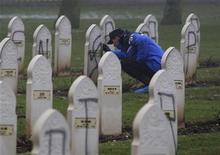 <p>A French gendarme looks for clues next to Muslim graves desecrated with Nazi inscriptions and swastikas in Notre Dame de Lorette cemetery in Ablain Saint Nazaire, northern France, December 8, 2008. REUTERS/Pascal Rossignol</p>
