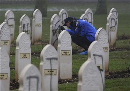 A French gendarme looks for clues next to Muslim graves desecrated with Nazi inscriptions and swastikas in Notre Dame de Lorette cemetery in Ablain Saint Nazaire, northern France, December 8, 2008. REUTERS/Pascal Rossignol