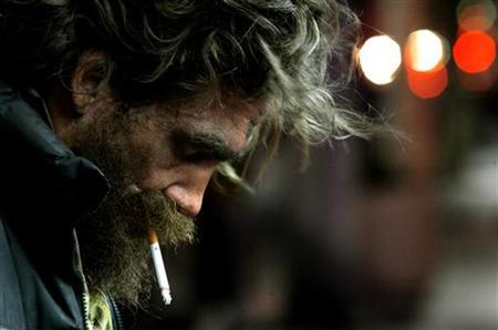 A homeless man smokes a cigarette on Hollywood Boulevard in Hollywood in this January 27, 2006 file photo. Homelessness and demand for emergency food are rising in the United States as the economy founders, a report said on Friday, and homeless advocates cautioned many cities were not equipped for the increase. REUTERS/Mario Anzuoni