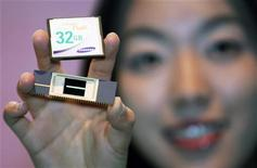 <p>Un'impiegata mostra una memoria flash Nand e un chip. REUTERS/Kim Kyung-Hoon (SOUTH KOREA)</p>