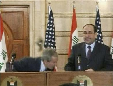 Video frame grab of President George W. Bush (L) ducking from a shoe during a news conference in Baghdad December 14, 2008. REUTERS/Reuters TV