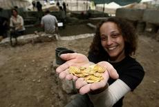 <p>Nadine Ross, a British volunteer for Israel's Antiquities Authority, holds coins she helped unearth during excavations in Jerusalem December 22, 2008. REUTERS/Ronen Zvulun</p>