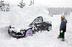 <p>Una donna osserva la sua auto ricoperta di neve nella stazione sciistica del Sestrière. REUTERS/Max Rossi</p>