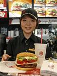"""<p>Una empleada de Burger King posa con una hamburguesa """"Whopper"""" durante un evento de prensa de la cadena en Tokio, 6 jun 2007. Los fanáticos de las hamburguesas que esperaban comer y oler a su plato favorito esta Navidad quedaron decepcionados, luego de que una nueva colonia de Burger King se convirtió en uno de los productos más difíciles de hallar durante las festividades de fin de año. REUTERS/Michael Caronna</p>"""