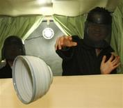 """<p>A customer with a protective gear smashes a dish to a wall inside a truck named """"The Venting Place"""" at Tokyo's Akihabara district December 20, 2008. Picture taken December 20, 2008. /Issei Kato</p>"""
